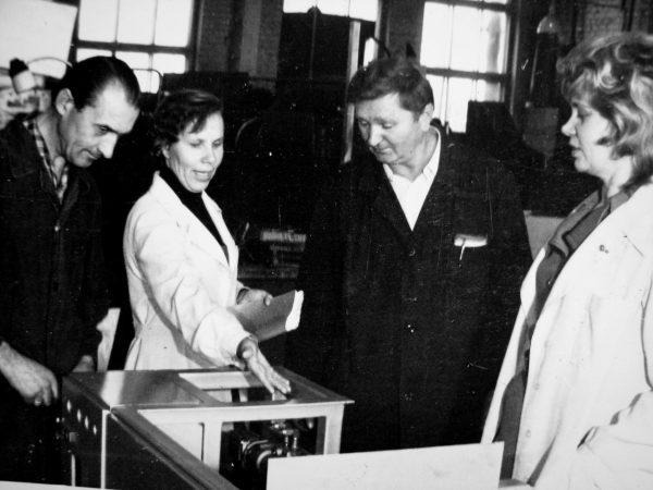 Šaltkalvis V. Nevulis, vadovaujančioji konstruktorė N. Kudrevičienė, cecho viršininkas A. Slušnys ir M. Stonkuvienė prie gaminamo M6-AUD bandomojo pavyzdžio