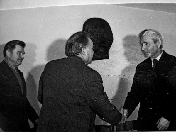 Jubiliatą A. Papečkį, sulaukusį užtarnauto poilsio, sveikina SKB vyr. inžinierius E. Ivanauskas ir A. Slušnys (kairėje)