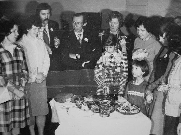 Konstruktorių padengtą stalą pristato N. Kudrevičienė – pirmoji kairėje. Už jos stovi B. Katkauskienė, nežin., K. Augustinas, J. Lenkauskienė, B. Juodagalvienė, L. Sakalauskaitė, mažesnioji mergaitė – Rūta Bernotaitė. 1978 m.
