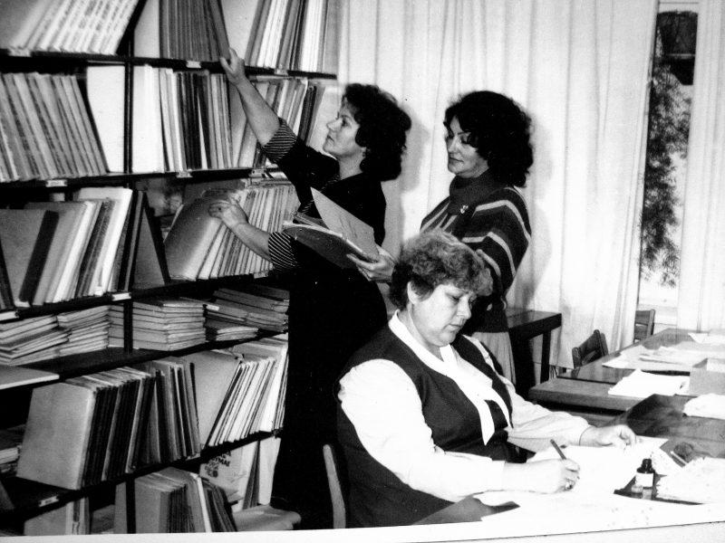 Techninio archyvo darbuotojos 1989 m. Sėdi R. Mickevičienė, prie lentynų archyvo vedėja J. Švirinienė ir D. Andriušaitienė