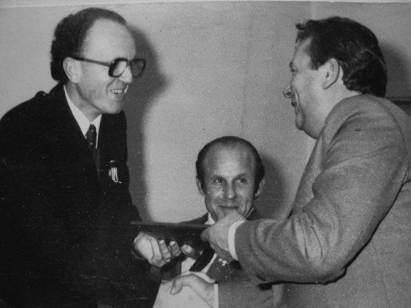 1984 m. spalio 29 d. MPA gamybinio susivienijimo generalinis direktorius J. Šeškevičius 25-mečio sveikinimą perduoda SKB viršininkui V. Mickevičiui